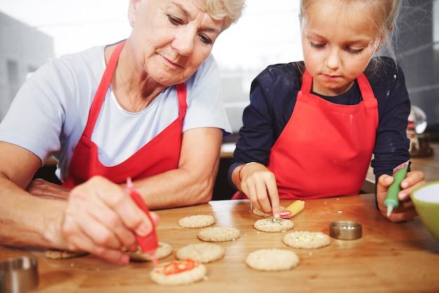 Nonna con ragazza che decora i biscotti di natale