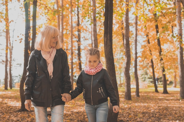 Grandmother with granddaughter in autumn park generation and family concept