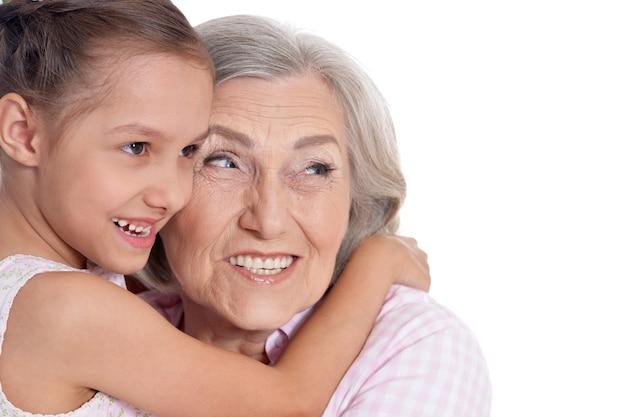 白い背景の上の彼女のかわいい孫娘と祖母