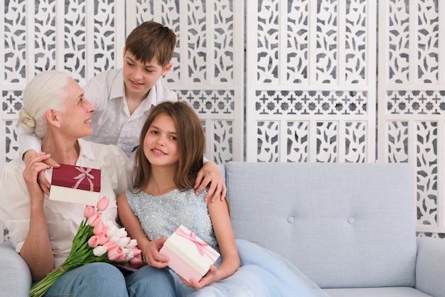 Бабушка с внуками держит подарочную коробку и букет цветов