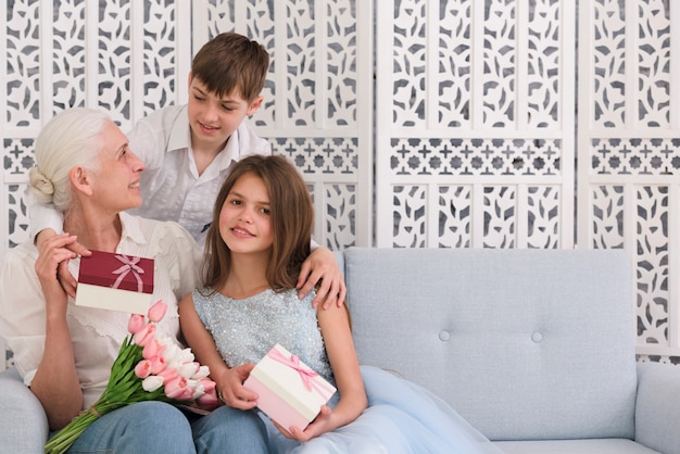 Grandmother with her grandchildren holding gift box and flower bouquet