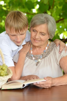 Grandmother with her grandson reading in summer at table