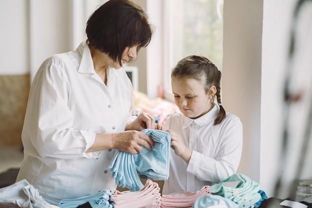 小さな孫娘と祖母が裁縫用の生地を測定します