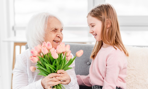 Бабушка с букетом тюльпанов в руках сидит с внучкой на диване и улыбается
