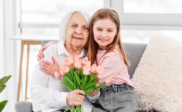 Бабушка с цветами тюльпанов в руках сидит на диване с внучкой и обнимает друг друга