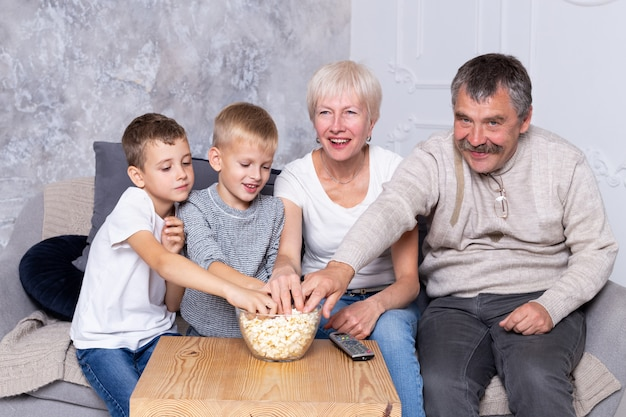 2人の孫を持つ祖母がテレビを見ています。家族はソファで一緒に映画を見て、ポップコーンを食べます