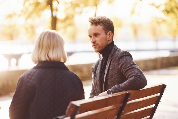Бабушка с молодым парнем в строгой одежде разговаривают в осеннем парке.