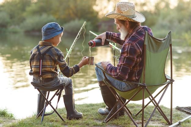 Дедушка и внук ловят рыбу и пьют чай