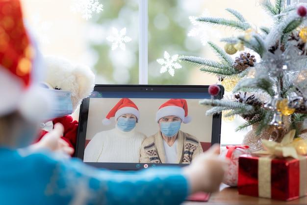 おじいちゃんとおばあちゃんがクリスマスツリーの装飾に対して窓辺のビデオチャットラップトップで挨拶