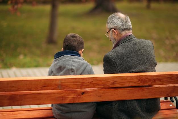 Дедушка и его внук вместе проводят время в парке. они сидят на скамейке. прогулка в