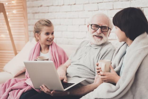 Дедушка и дети смотрят фильм с кружками чая.