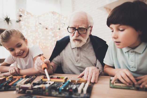 Grandpa examines pc board curious kids watching.