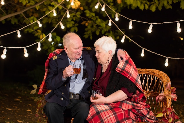 Grandpa and grandma drink tea in the park