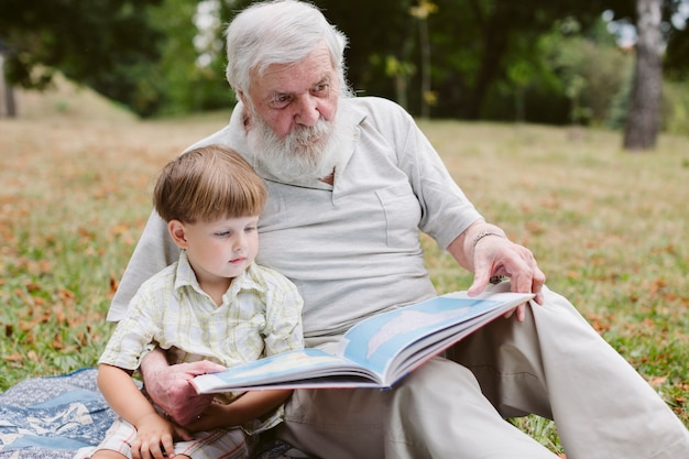 Grandpa and grandson in park reading