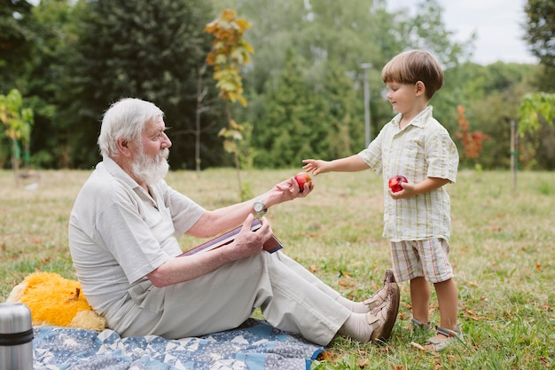Grandpa and grandson at picnic in nature