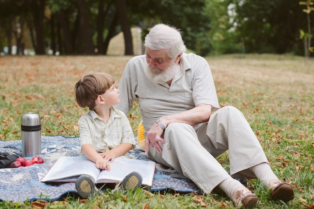 Grandpa and grandson at picnic reading