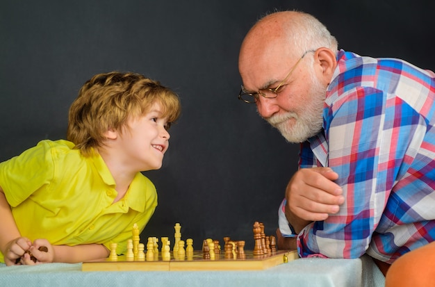 Grandpa and grandson playing chess enjoying leisure time chess match board games handsome