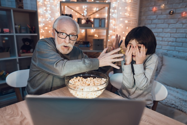 Grandpa grandson watching scary movie on laptop