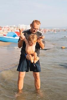 Grandpa holding grandson on top of sea