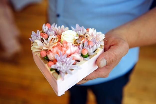 おじいちゃんの手に結婚指輪を保持して、クローズアップ。新婚夫婦のリングの上に横たわる花の枕を持つ老人の手。祖父母の日コンセプト