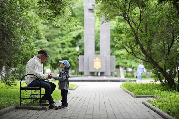 Дедушка гуляет с внуком в весеннем парке. внук и дедушка на прогулке. дедушка разговаривает с маленьким мальчиком.