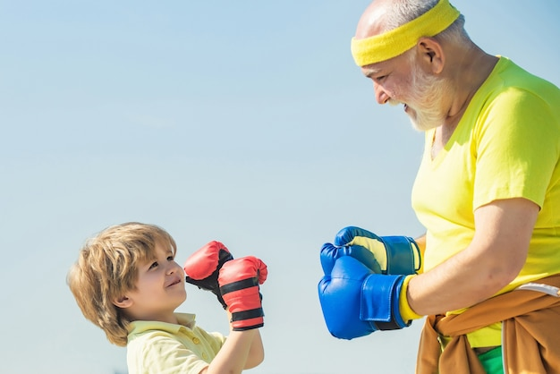 Grandpa and little child boy in boxing stance doing exercises with boxing gloves