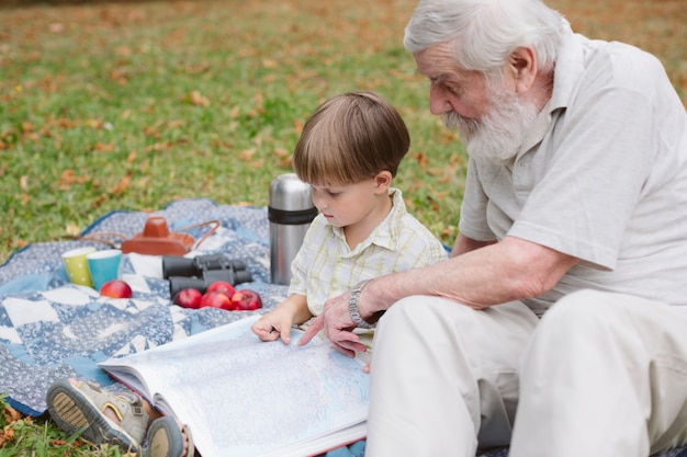 Grandpa showing picture on book to grandson