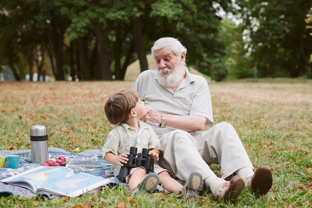 Grandpa teaching grandson about binocular