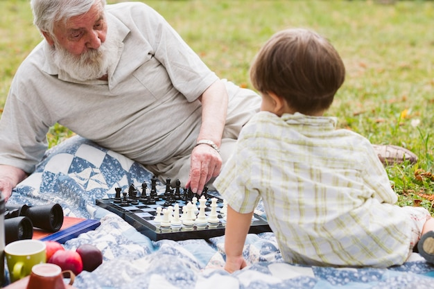 Grandpa teaching grandson chess