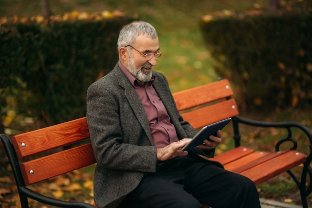 Grandpa use a tablet sitting in the pakr on the bench