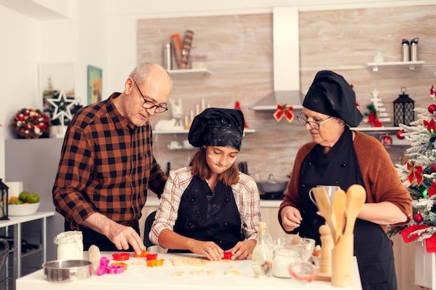 伝統的なデザートを作るクリスマスの日の祖父母と孫娘