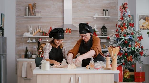 エプロンを持った孫が自家製クッキーを準備している間、祖父母は冬休みを楽しんでいます