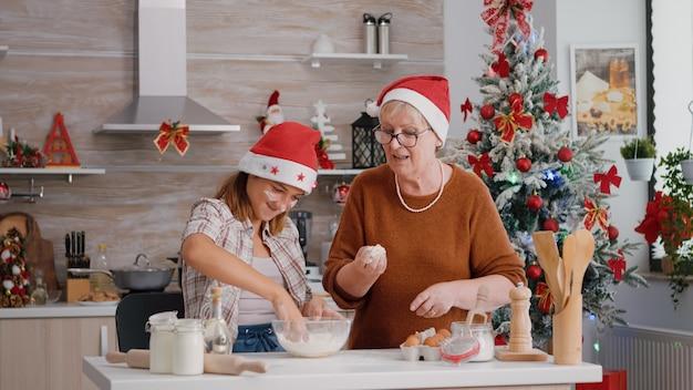 Дедушка и бабушка помогают внуку готовить домашнее традиционное тесто для печенья на кулинарной кухне