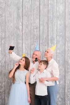 Grandparent wearing party hat taking selfie on mobile phone with their grandchildren holding paper props
