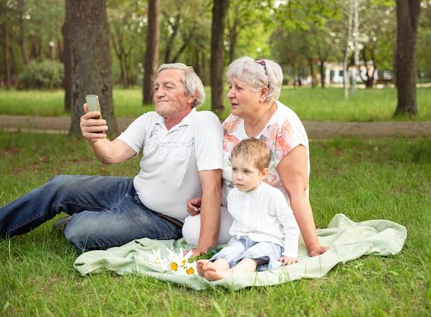 Дедушка и бабушка с внуком с помощью планшета для видеосвязи с семьей