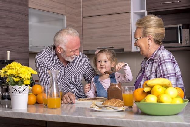 부엌에서 초콜릿 크림으로 팬케이크를 준비하는 조부모와 손녀