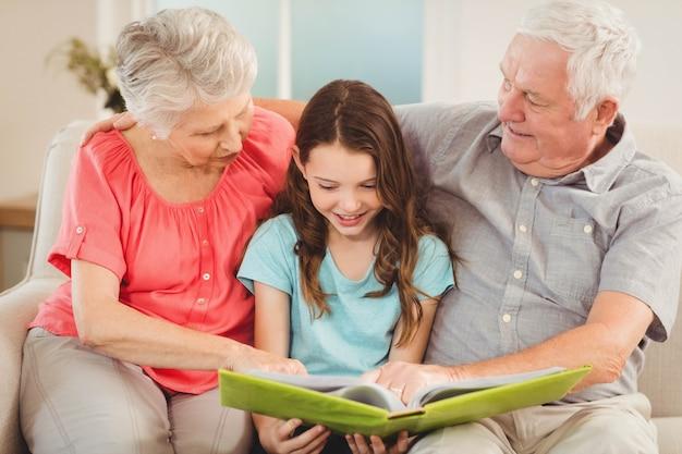 Бабушка и дедушка и внучка сидят на диване и читают книгу с внучкой