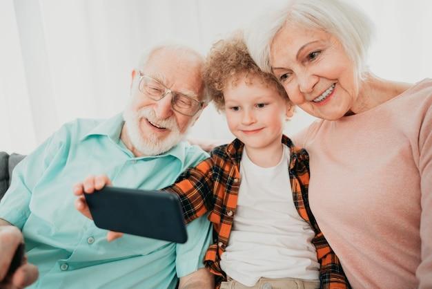 祖父母と孫が家で遊ぶ-家で家族、甥の世話をする祖母と祖父