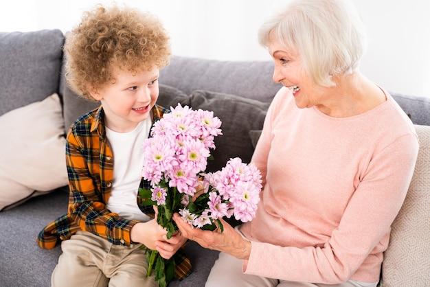 祖父母と孫が家で遊ぶ-家で家族、甥の世話をする祖母