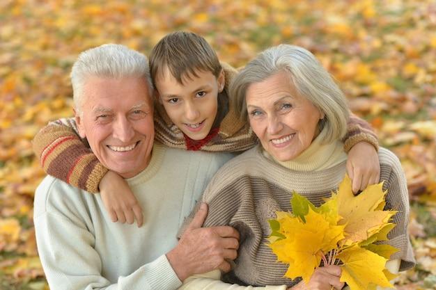 Бабушка и дедушка и внук вместе в осеннем парке