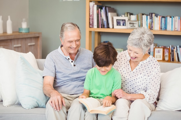 Grandparents assisting grandson while reading book in sitting room