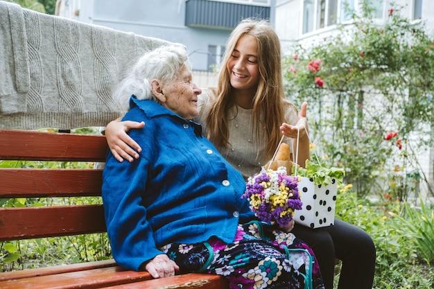 День бабушки и дедушки воссоединения семейного единения старшая старая бабушка обнимает внучку на открытом воздухе