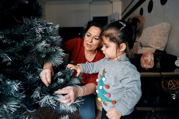 祖父母は小さな孫娘でクリスマスツリーを飾ります