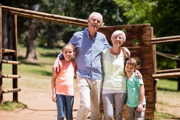 Бабушка и дедушка вместе проводят время со своими внуками в парке