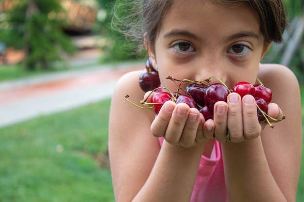 Grandparents feed the child with cherries.selective focus.nature
