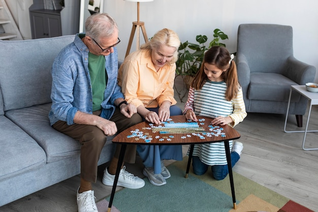 Grandparents and girl doing puzzle full shot