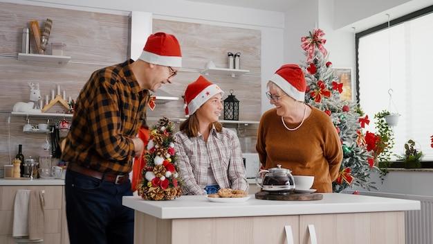 祖父母が孫娘にリボン付きのラッパークリスマスプレゼントを贈る