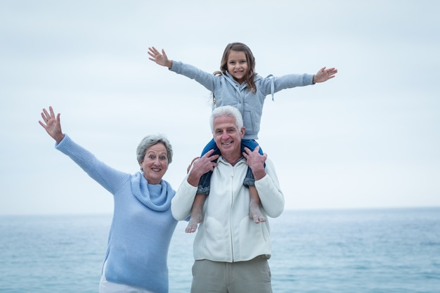 Grandparents and granddaughter with arms outstretched at beach