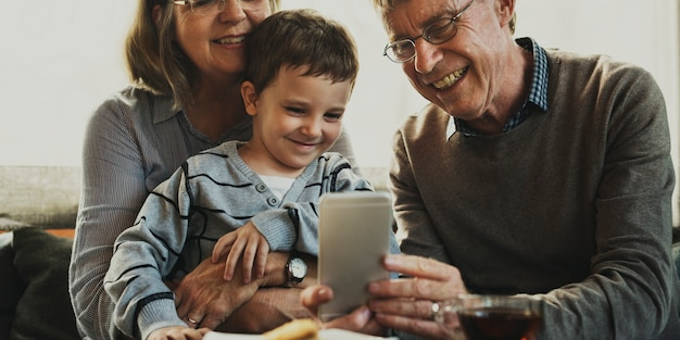 Grandparents and grandson using mobile phone