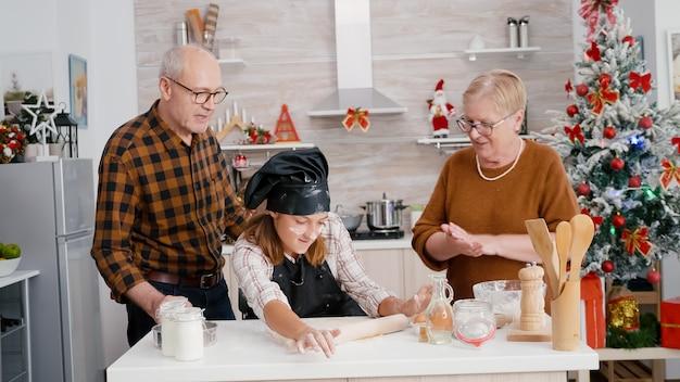 손녀가 전통적인 수제 반죽을 준비하는 것을 돕는 조부모